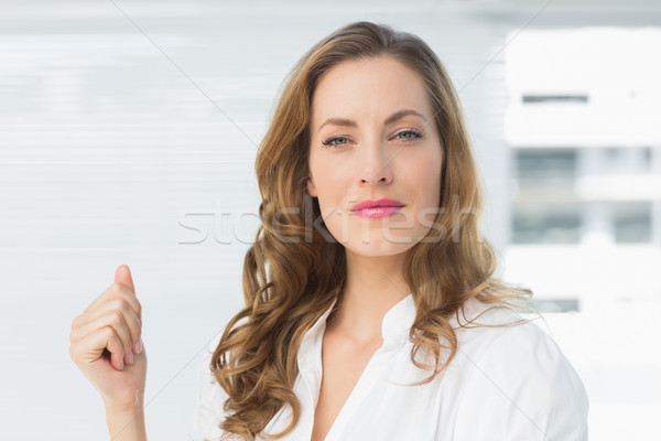 Stock photo: Smiling young businesswoman against blinds
