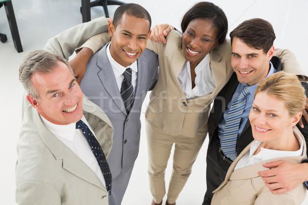 Zárt üzleti csapat átkarol mosolyog felfelé kamera Stock fotó © wavebreak_media