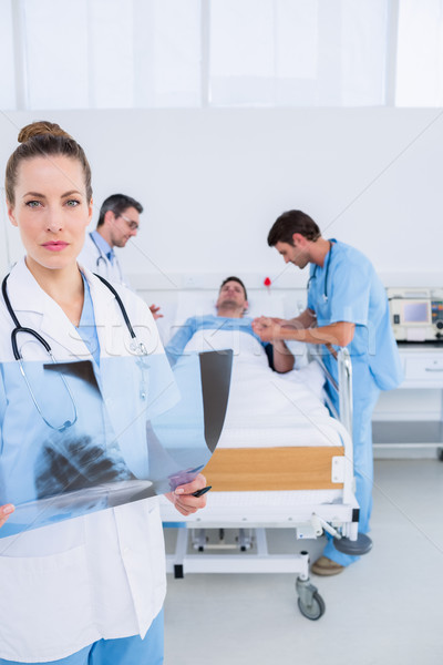 Doctor holding xray with colleagues and patient in hospital Stock photo © wavebreak_media