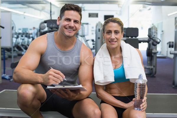 Female bodybuilder sitting with personal trainer smiling at came Stock photo © wavebreak_media