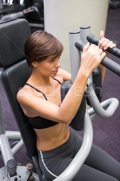 Fókuszált barna hajú súlyok gép karok tornaterem Stock fotó © wavebreak_media