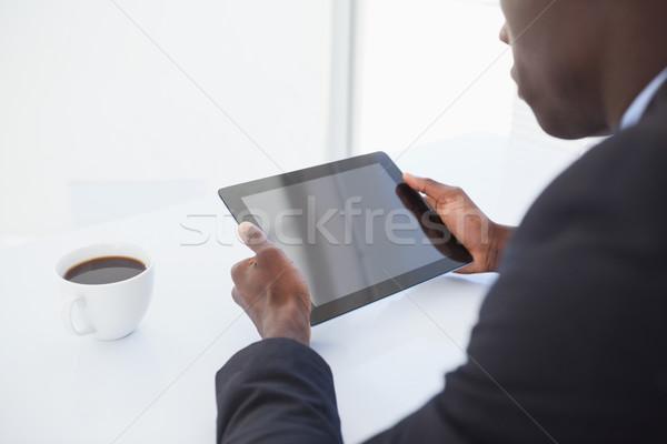 Focused businessman looking at his tablet Stock photo © wavebreak_media