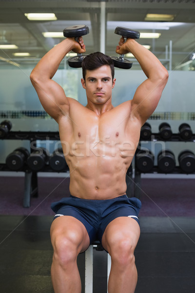 Muscular man exercising with dumbbells in gym Stock photo © wavebreak_media