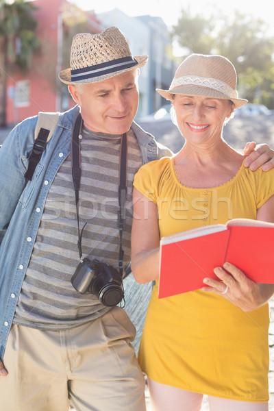 Happy tourist couple using guide book in the city  Stock photo © wavebreak_media