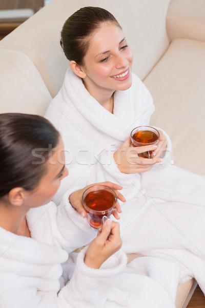 Smiling women in bathrobes having tea Stock photo © wavebreak_media