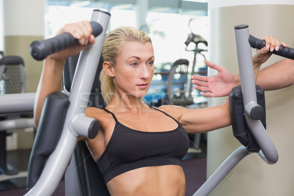 Fit young woman using fitness machine at gym Stock photo © wavebreak_media