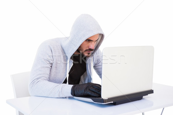 Serious burglar hacking into laptop Stock photo © wavebreak_media