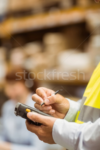 Close up of manager wearing yellow vest using handheld Stock photo © wavebreak_media