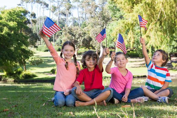 Happy little friends waving american flag Stock photo © wavebreak_media