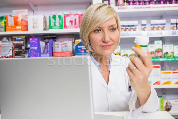 Sonriendo farmacéutico mirando medicina farmacia mujer Foto stock © wavebreak_media