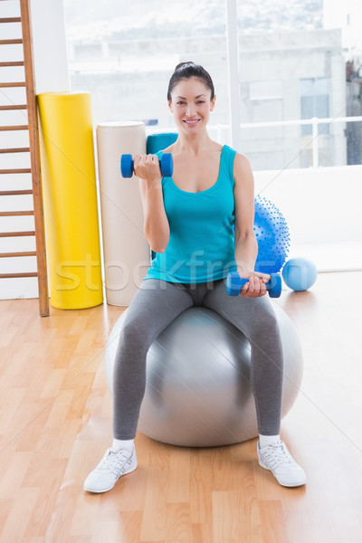 Stock photo: Smiling young woman exercising with dumbbells on fitness ball
