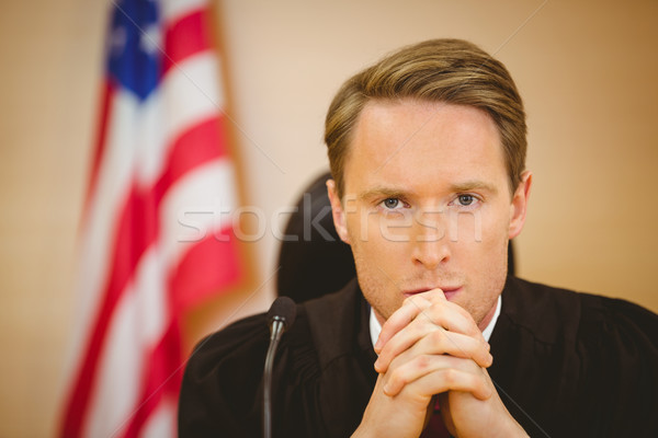 Stock photo: Portrait of a serious judge with american flag behind him