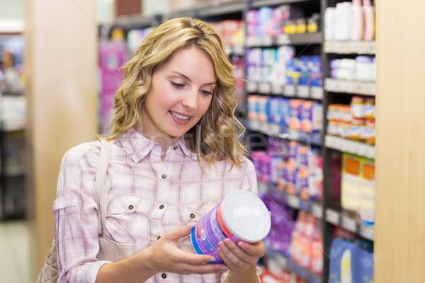 Sorridere bella donna bionda guardando prodotto supermercato Foto d'archivio © wavebreak_media