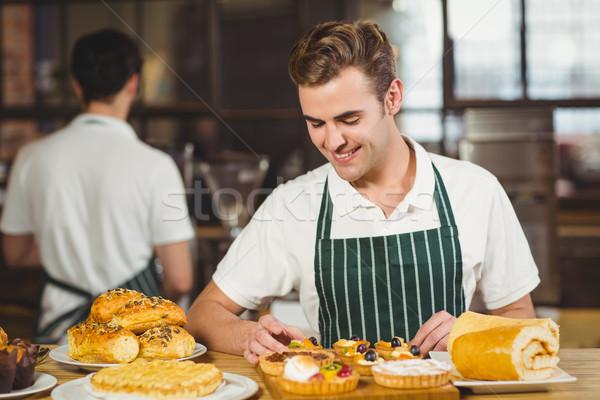 Smiling waiter tidying up the pastries Stock photo © wavebreak_media