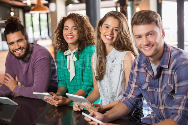 Portrait of friends holding digital tablets in restaurant Stock photo © wavebreak_media