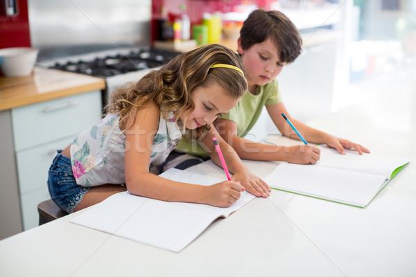 Siblings doing homework in kitchen Stock photo © wavebreak_media