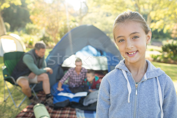 Girl smiling at camera while family sitting at tent in background Stock photo © wavebreak_media