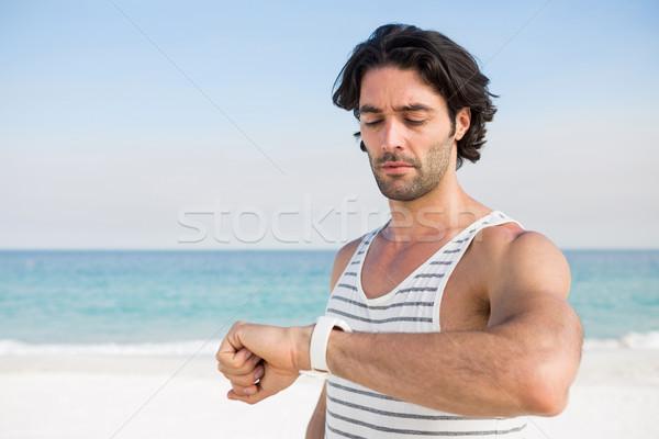 Man looking at wristwatch while against sea Stock photo © wavebreak_media