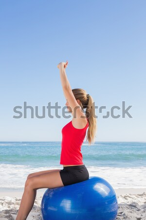 Young woman with eyes closed exercising on mat at beach Stock photo © wavebreak_media