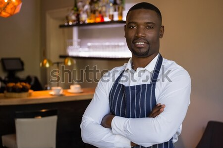 Portrait of bar tender standing with arms crossed at bar counter Stock photo © wavebreak_media