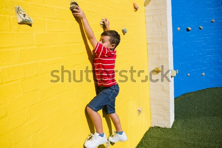 Rear view of boy climbing on yellow wall Stock photo © wavebreak_media