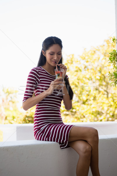 Woman drinking cocktail while sitting on retaining wall Stock photo © wavebreak_media