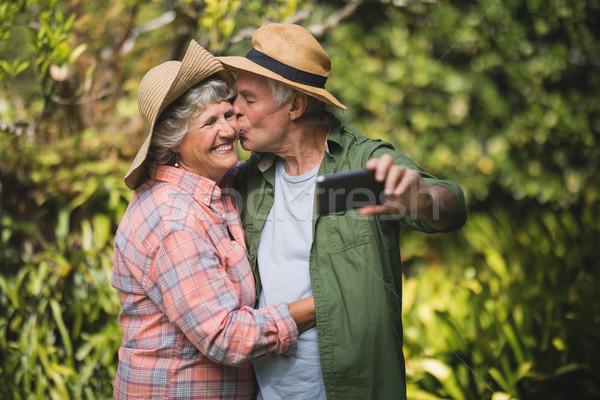 Senior uomo bacio donna sorridente albero Foto d'archivio © wavebreak_media