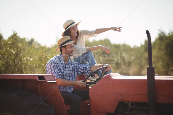 Cheerful woman gesturing away while sitting with boyfriend on tractor Stock photo © wavebreak_media
