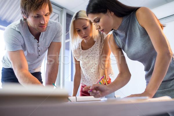 Architects working on blueprint at their desk Stock photo © wavebreak_media