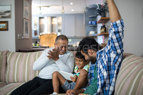 Happy grandfather and father with boy sitting on sofa Stock photo © wavebreak_media