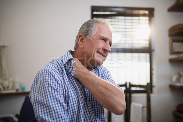Senior male patient grimacing with neck pain Stock photo © wavebreak_media