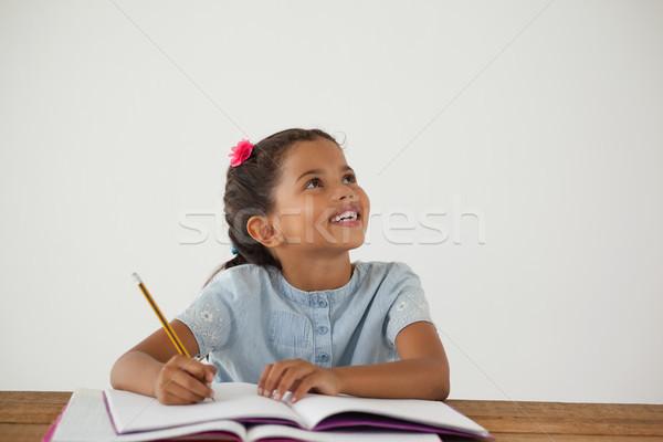 Jeune fille écrit livre blanche portrait enfant Photo stock © wavebreak_media