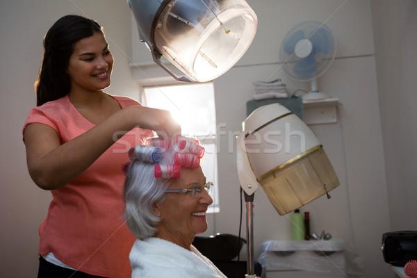 Smiling beautician removing curlers from senior woman hair Stock photo © wavebreak_media