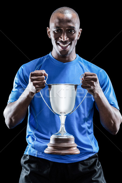Portrait of happy sportsman holding trophy Stock photo © wavebreak_media