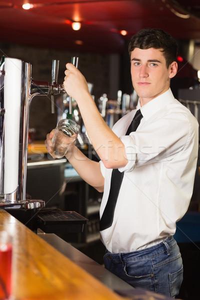 Portrait of barkeeper holding glass at beer dispenser Stock photo © wavebreak_media