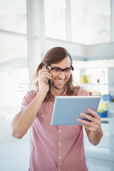Hipster using mobile phone while looking at digital tablet Stock photo © wavebreak_media