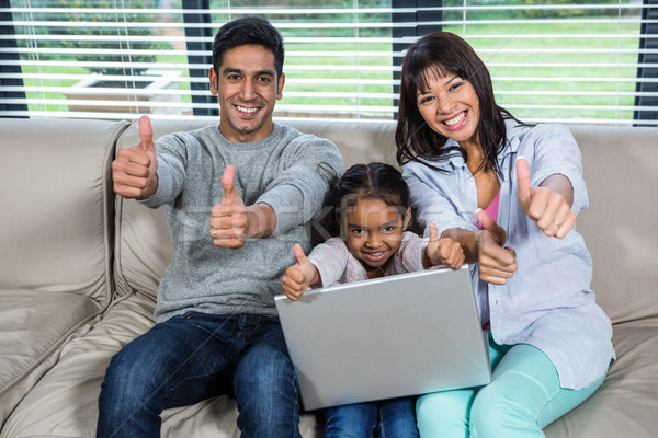 Happy young family using laptop with thumbs up Stock photo © wavebreak_media