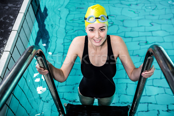 Stock photo: Smiling swimmer woman getting out of the swimming pool