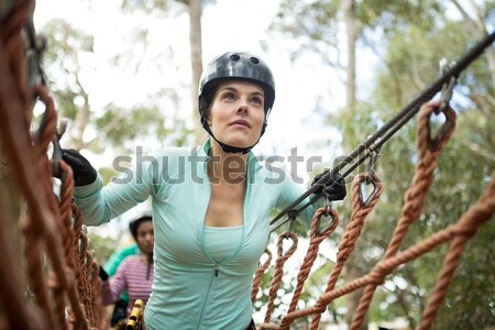 Smiling woman wearing safety helmet holding zip line cable in the forest Stock photo © wavebreak_media