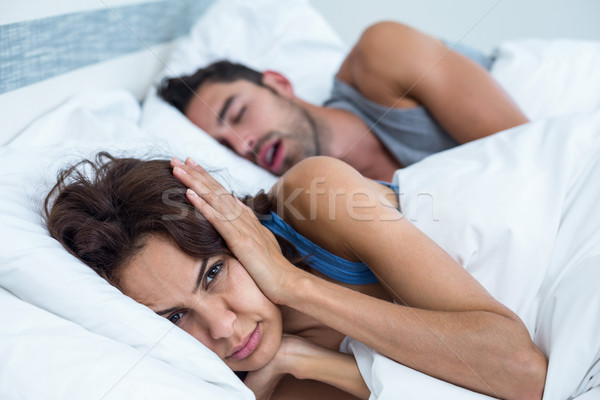 Woman blocking ears with hands while man snoring on bed Stock photo © wavebreak_media