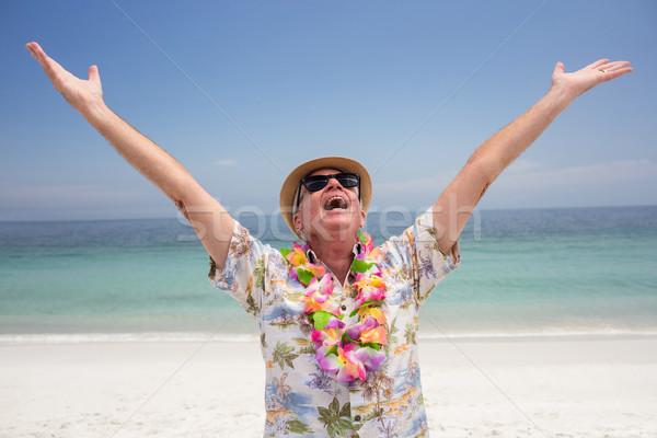 Happy senior man wearing flower garland and enjoying on the beac Stock photo © wavebreak_media