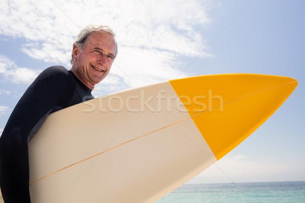 Portrait of senior man in wetsuit holding a surfboard Stock photo © wavebreak_media