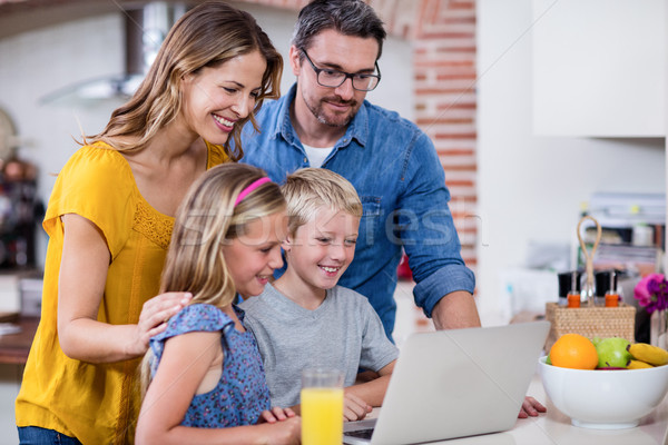 Parents and kids using laptop in kitchen Stock photo © wavebreak_media