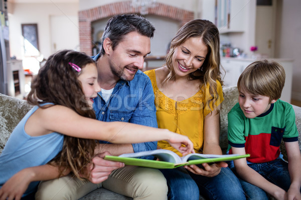 Happy family looking at a photo album Stock photo © wavebreak_media