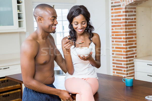 Young woman having breakfast cereal while man standing beside he Stock photo © wavebreak_media