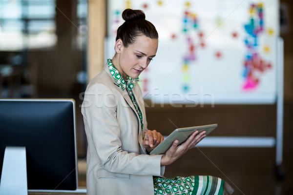 Businesswoman sitting on her desk Stock photo © wavebreak_media