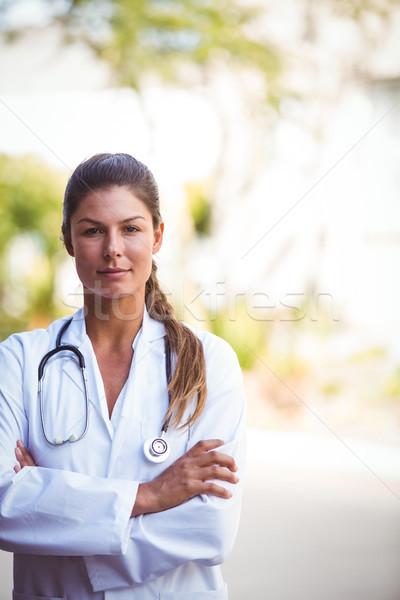 Retrato enfermera grave mirar los brazos cruzados fuera Foto stock © wavebreak_media
