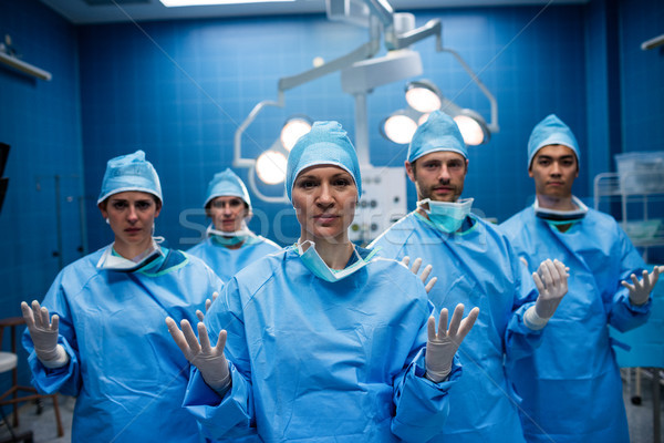 Portrait of surgeons standing with hands raised in operation roo Stock photo © wavebreak_media
