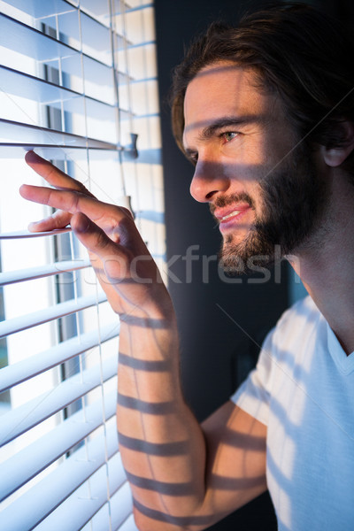 Stock photo: Man looking through window blinds after waking up