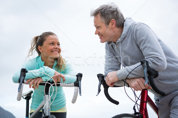 Couple leaning on bicycle while interacting with each other Stock photo © wavebreak_media